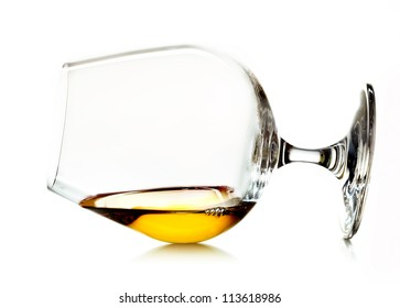 Glowing golden cognac or brandy in a snifter glass lying on its side on a white background