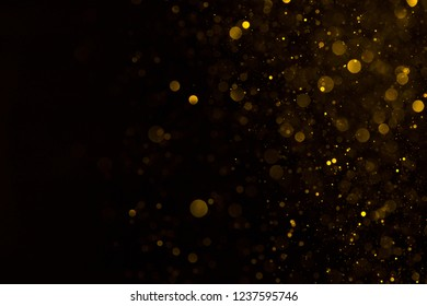 Glowing golden dust spark particles falling on black background