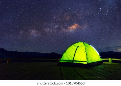 Glowing green camping tent on bamboo terrace under the night sky full of stars and the Milky Way, Baan Jabo, Mae Hong Son, Thailand. leisure tourists.