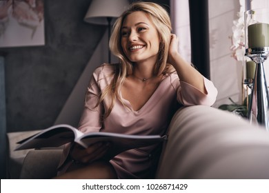 Glowing with happiness. Attractive young woman in elegant dress keeping hand in hair and smiling while sitting on the sofa
