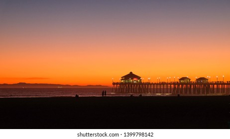 A glowing horizon after sunset over the Huntington Beach Pier in California.