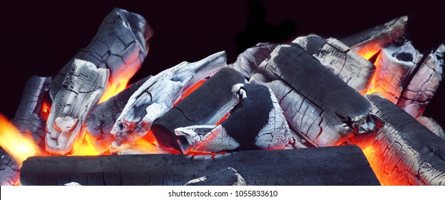 Glowing Hot Charcoal Isolated On Black Background With Copy Space, Front View, Close up. Concept For BBQ grill, Open Fireplace, Bonfire, Campfire, Hearth, Fireside, Chimney. Abstract Web Banner