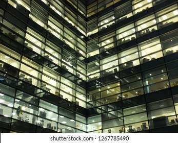 glowing illuminated windows in a large modern geometric city office building at night showing work spaces and desks
