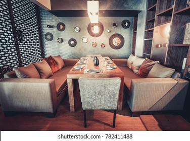 Glowing interior in a loft modern style restaurant with served wooden table and comfortable sofas. Private room. Vintage instagram Color filter toning