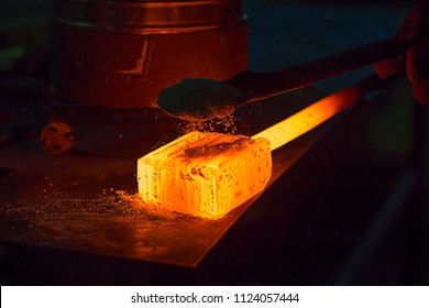 Glowing iron ingot on the table. Hot metal workpiece for the manufacture of Damascus steel.