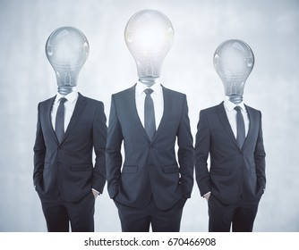 Glowing lamp headed businessmen on concrete background. Inovation concept