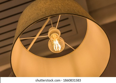 Glowing lampshade made of textile ceiling mount. A warm yellow incandescent light is on. Concept of interior decoration. Indoor.