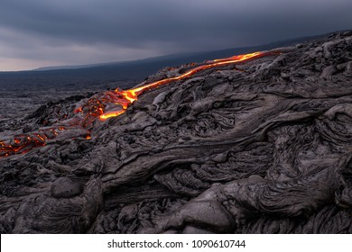 Glowing lava flow from Puu Oo in the evening on the Pali in Kalapana, Big Island, Hawaii.
