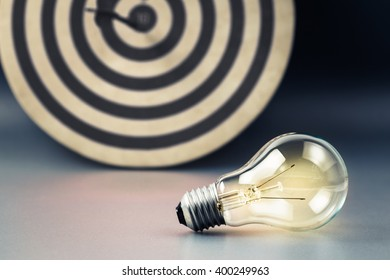 Glowing light bulb with accurate dart on target