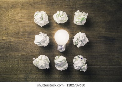 Glowing light bulb among the crumpled paper balls, success come from failures and mistakes
