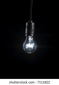 A glowing light bulb in the darkness hanging on a cable.