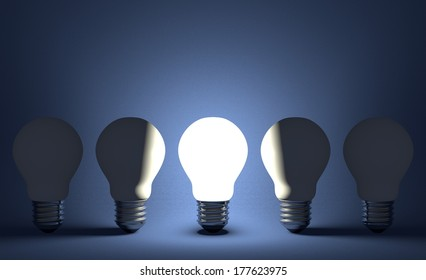 Glowing light bulb in row of switched off ones on dark blue textured background. Front view