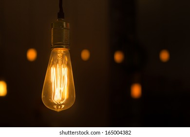 Glowing lightbulb dangling from the ceiling