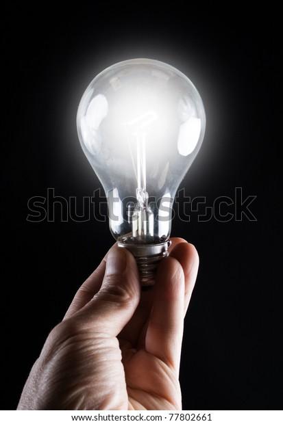 Glowing lightbulb in a hand