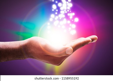 Glowing Lights Flowing From An Open Hand Against Colorful Circle Backdrop