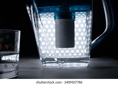 Glowing with many lights decanter for water purification is filled with purified water through a filter, there is a glass of purified water.