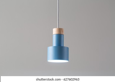 Glowing metal blue lamp with light wooden part is hanging on the white cable on the gray background. Closeup photo. Horizontal.