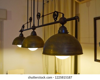 Glowing metal lamps in a classical industrial design hanged in a dining room