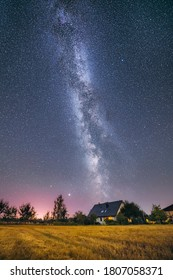 Glowing milky way over crop field covered in fog. Starry night at farmstead. Farm house and tractor.