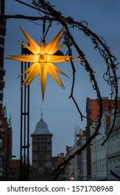 Glowing Moravian Christmas star and street decoration in front of the Burgtor, a city gate in the old town of Luebeck at dusk, selected focus, blurry background