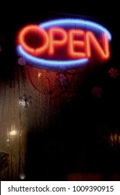 Glowing neon lighted red and blue open sign on business,  seen through rain wet window at night
