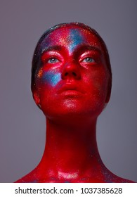 Glowing neon makeup with dramatic look in his eyes. Creative body art on the theme of space and stars. Amazing close-up portrait glow in the bright dark makeup