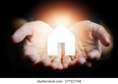 glowing open hands with house