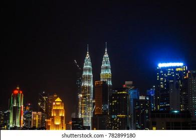 The glowing Petronas Twin Towers in the dark night sky of Kuala Lumpur city, Malaysia. The Petronas Towers, also known as the Petronas Twin Towers, are twin skyscrapers in Kuala Lumpur, Malaysia.