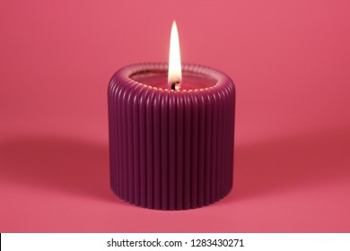 Glowing purple cande on bright pink background. Composition in gorgeous neon colors with a decorative object .  Romantic and relaxing atmosphere created by the candelight.