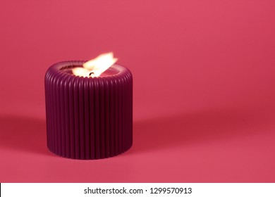 Glowing purple cande on bright pink background with space for copy. Composition in gorgeous neon colors with a decorative object .  Romantic and relaxing atmosphere created by the candelight.