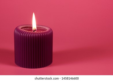 Glowing purple cande on bright pink background with space for copy. Composition in gorgeous neon colors with a decorative object. Romantic and relaxing atmosphere created by the candelight.