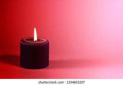Glowing purple cande on gradient pink background with space for copy. Composition in gorgeous neon colors with a decorative object. Romantic and relaxing atmosphere created by the candelight.