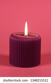 Glowing purple cande on gradient pink background. Composition in gorgeous neon colors with a decorative object. Romantic and relaxing atmosphere created by the candelight.