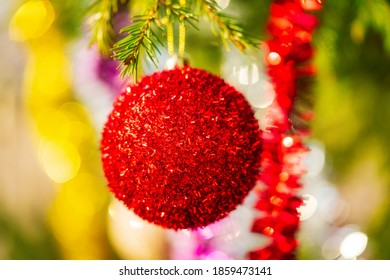 Glowing red Christmas ball and colorful shining tinsel hanging on branch of tree. Close-up view Xmas festive composition for Happy New Year. Selective focus in foreground, blurry bokeh in background.