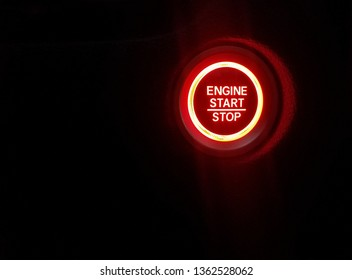 glowing red engine start stop light and black background