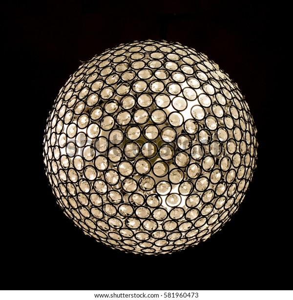 Glowing round chandelier (lamp) on a dark background