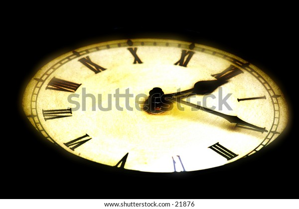 Glowing, selective focus antique clock. Black background.