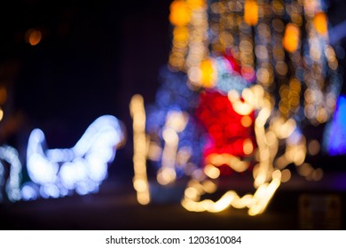 Glowing silhouette of a deer on a Christmas decorated street