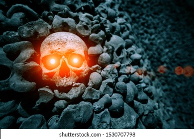 Glowing skull in a pile of bones. Horror and fear