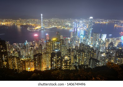 Glowing skyscrapers along Victoria Harbour in Hong Kong at night