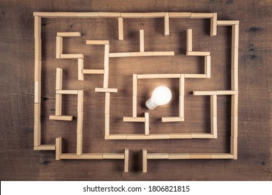 Glowing small light bulb as the goal of the maze game built by wood blocks toy on the table, finding the correct direction to the success and creativity