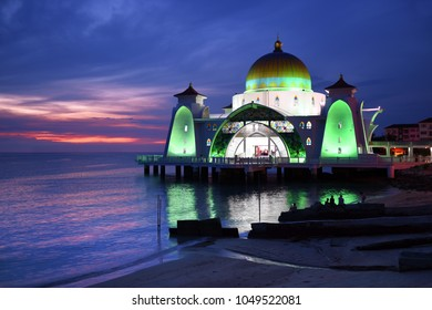 Glowing Strait Mosque of Malacca during sunset and blue hour. The so called swimming Mosque is located at the Historical Malacca City, Malaysia.
