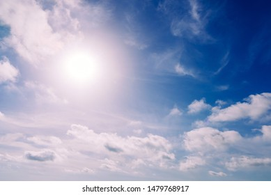 Glowing sun in a blue summer sky with nice white clouds.