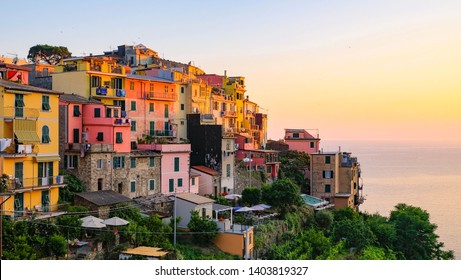 A glowing sunset lights up the colorful buildings in the Cinque Terre village of Corniglia, Italy.