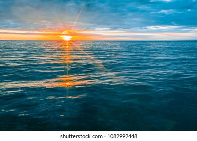 Glowing sunset set over calm bay water