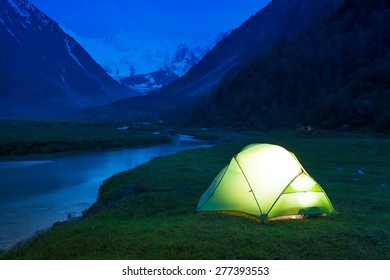 Glowing tent stands on the banks of a mountain stream, amid high mountains and snow-capped peaks. Twilight, night.