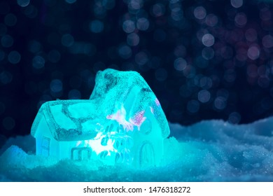 Glowing toy house in the snow on the background of Christmas lights. Festive, Christmas or New Year concept
