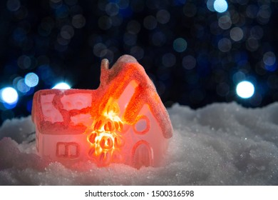 Glowing toy house in the snow on the background of Christmas lights. Festive, Christmas or New Year concept.