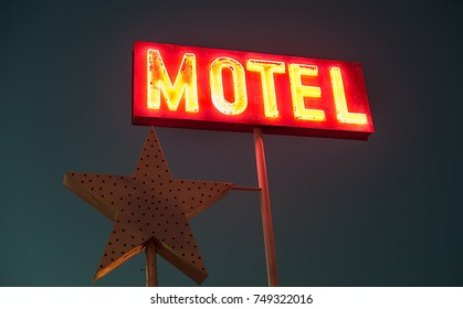 Glowing vintage old motel sign at night