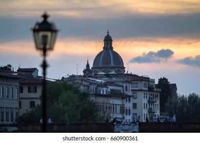 Glowing vintage street lamp on background with Arno river, Florence, Italy